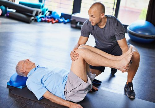 Physical therapist working with a senior man's legs