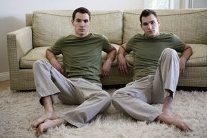 Adult twin men in matching green shirts and khaki pants sit on the floor and lean against a couch