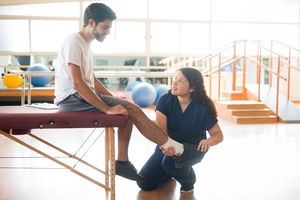 Physical therapist holding and checking patient's leg