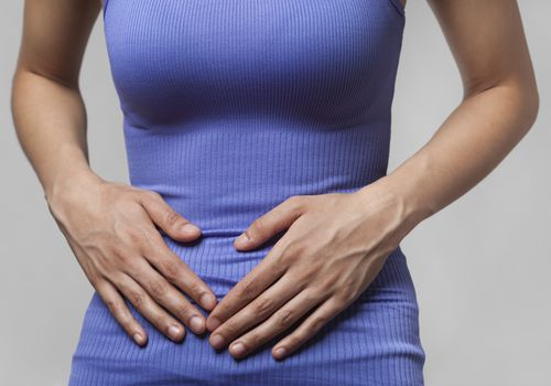 Woman with hands over abdomen and pelvic area