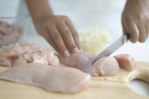 Girl's hand slicing raw chicken breast on chopping board