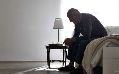 Man hunched over bed