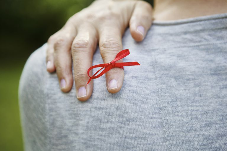 Red ribbon tied on index finger