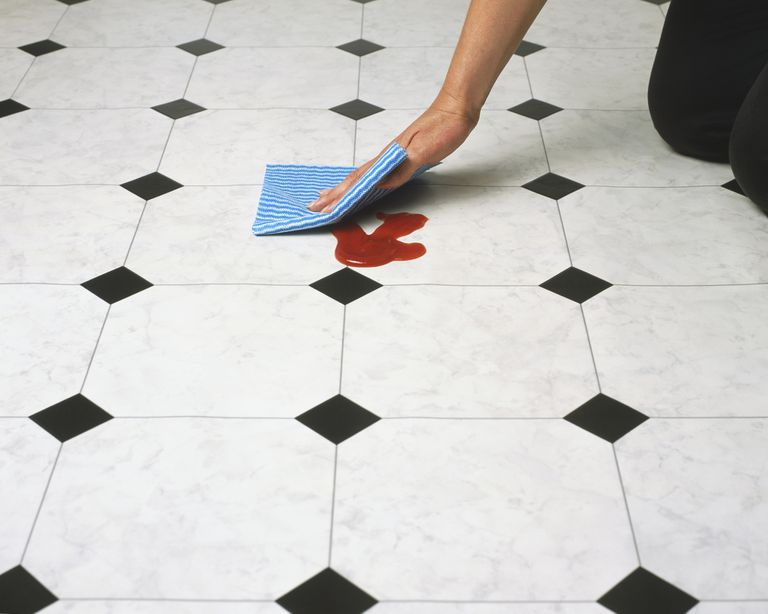 Wiping tomato ketchup off a tiled floor, close up, high angle view.