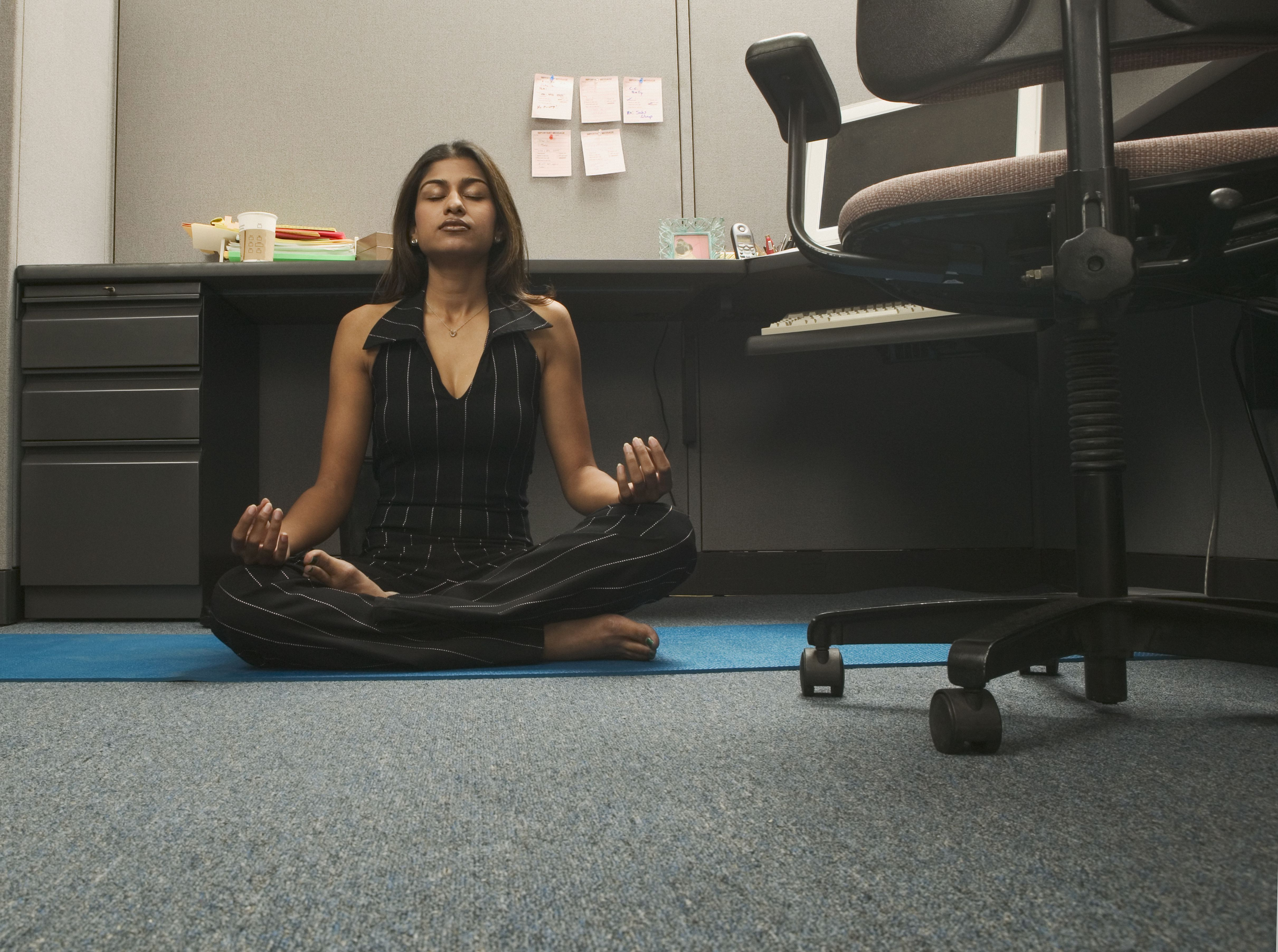 Young woman practicing yoga in office