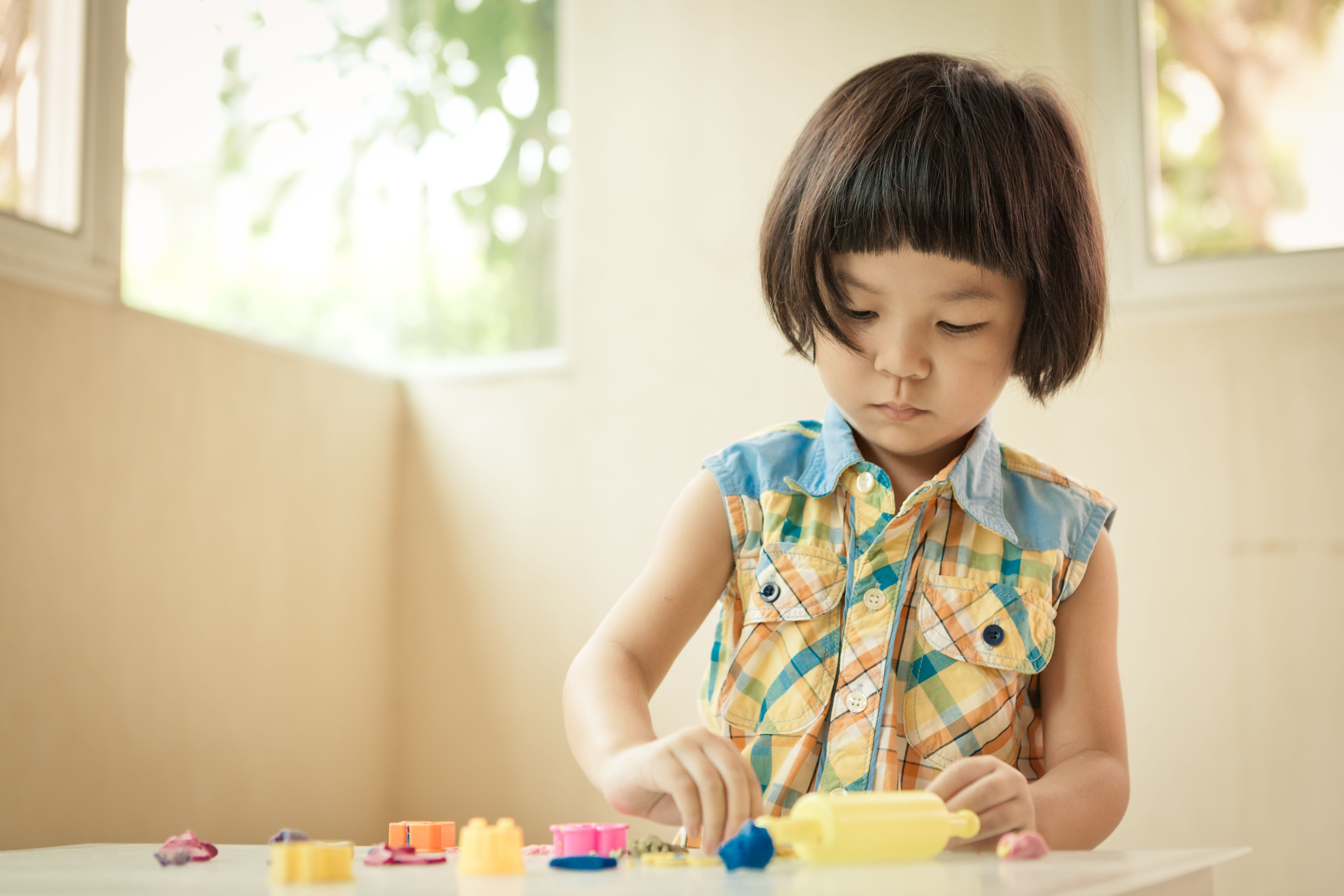 Little girl playing with he play dough