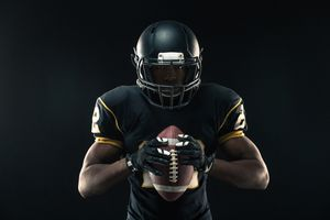 Portrait of a Black American football player on a black background.