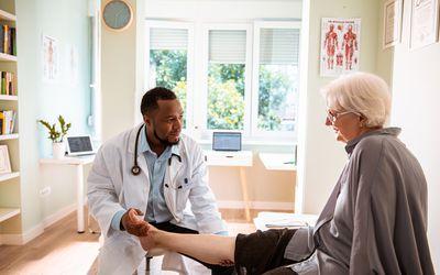 Doctor examines a senior woman's leg.