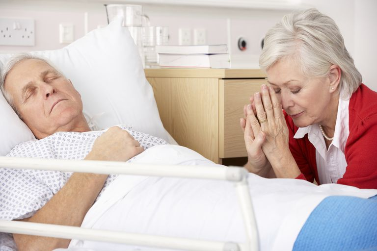 photo of a woman praying at the bedside of a dying man