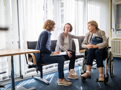Therapist discussing with women in waiting room