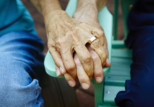 Close up of older people holding hands