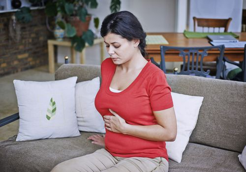Woman suffering from abdominal pain sitting on couch