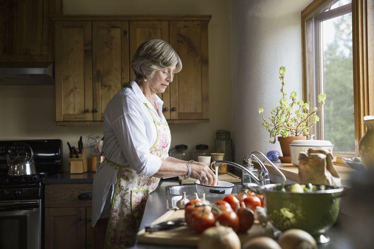 senior woman washing vegetables at sink