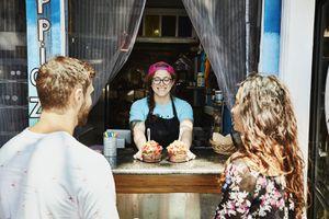 Smiling owner of juice bar serving organic acai bowls to customers sitting at bar
