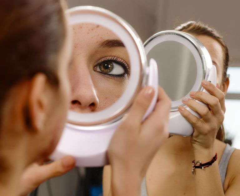 Teenage girl looking at face in mirror