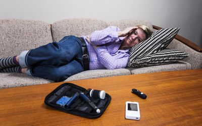 Woman with diabetes lying down from a headache associated with low blood sugar