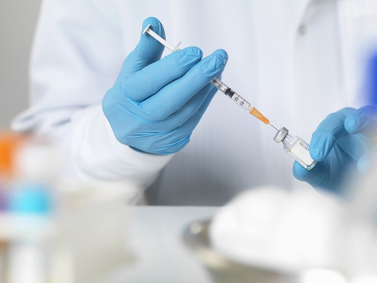 doctor in lab filling syringe with vaccine