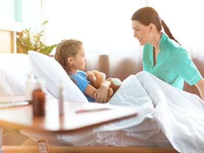 Nurse attending child in bed