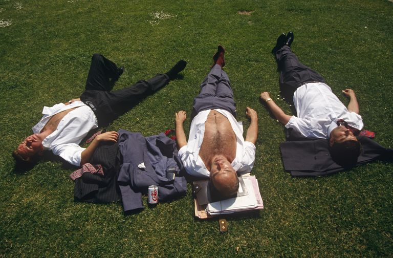 Three city office workers sunbathe during hot lunchtime