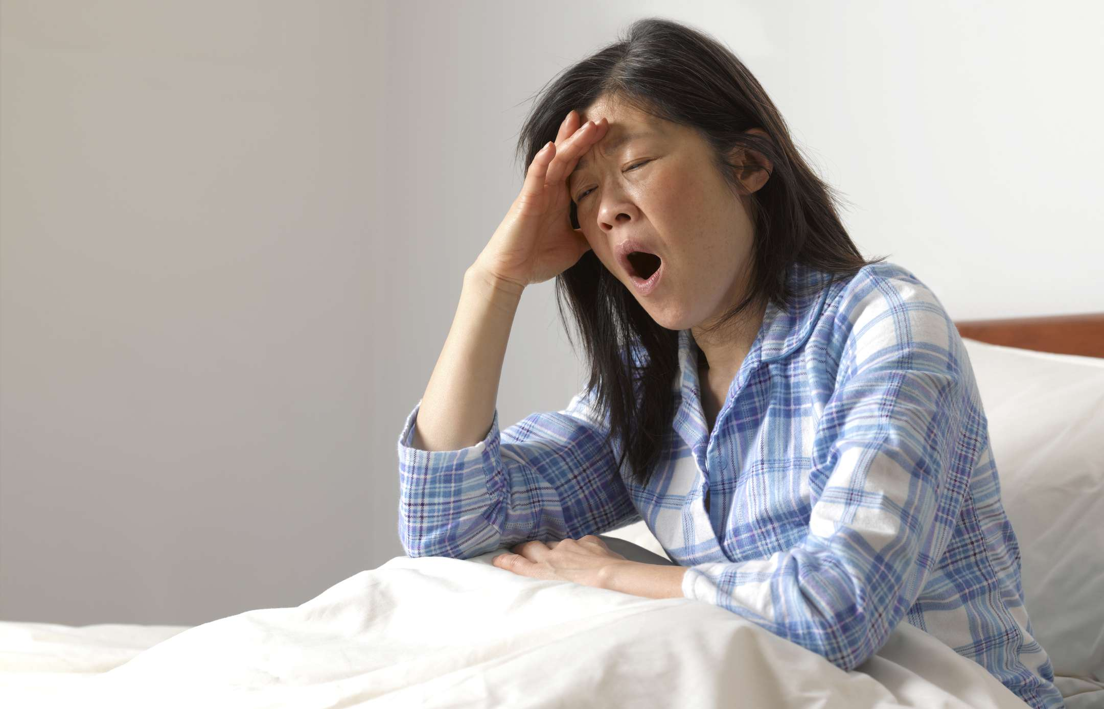 A woman sitting up and yawning in bed