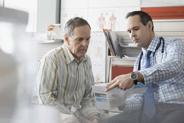 Doctor showing senior patient brochure in office