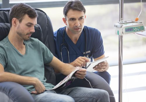 Doctor holding digital tablet, talking to patient undergoing medical treatment in hospital