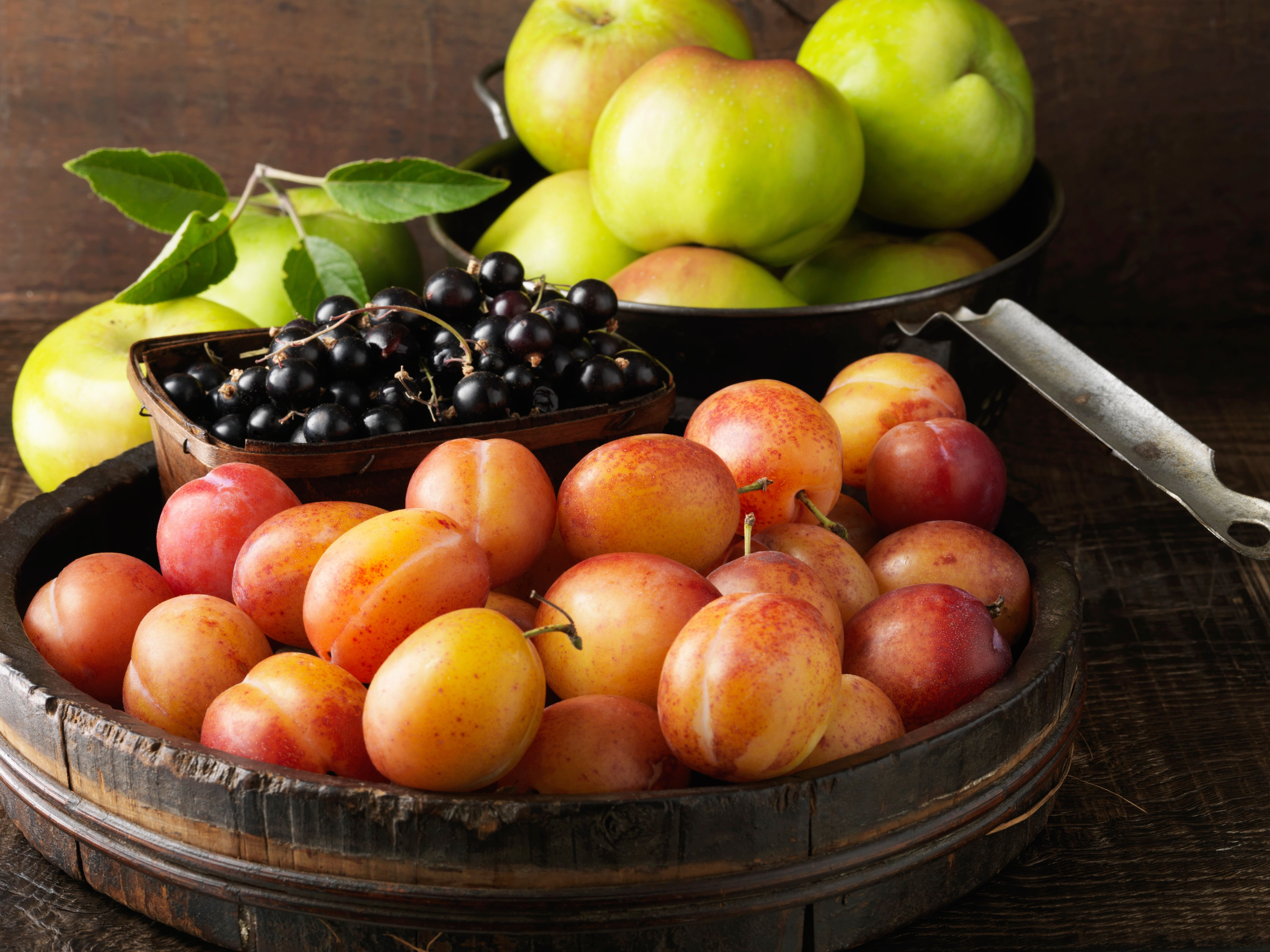Apples, cherries, and nectarines arranged on wooden surface