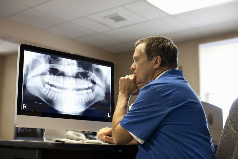 Dentist viewing x-ray on computer screen
