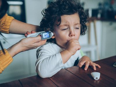 Mother with ear thermometer checking coughing child's temperature