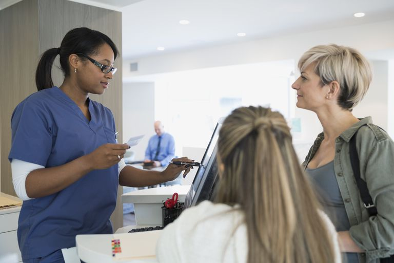 Nurse checking patient in at computer clinic lobby