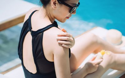 Young Asian woman applying suntan lotion while sunbathing by the swimming pool - stock photo