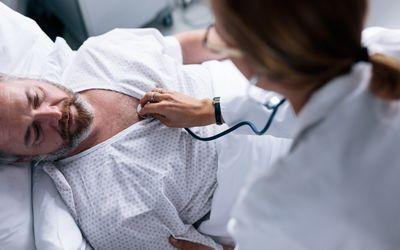 Doctor taking heartbeats of sick patient