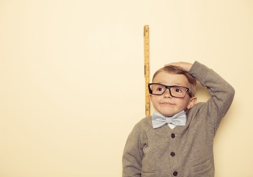 little boy with glasses and a bowtie measuring his height