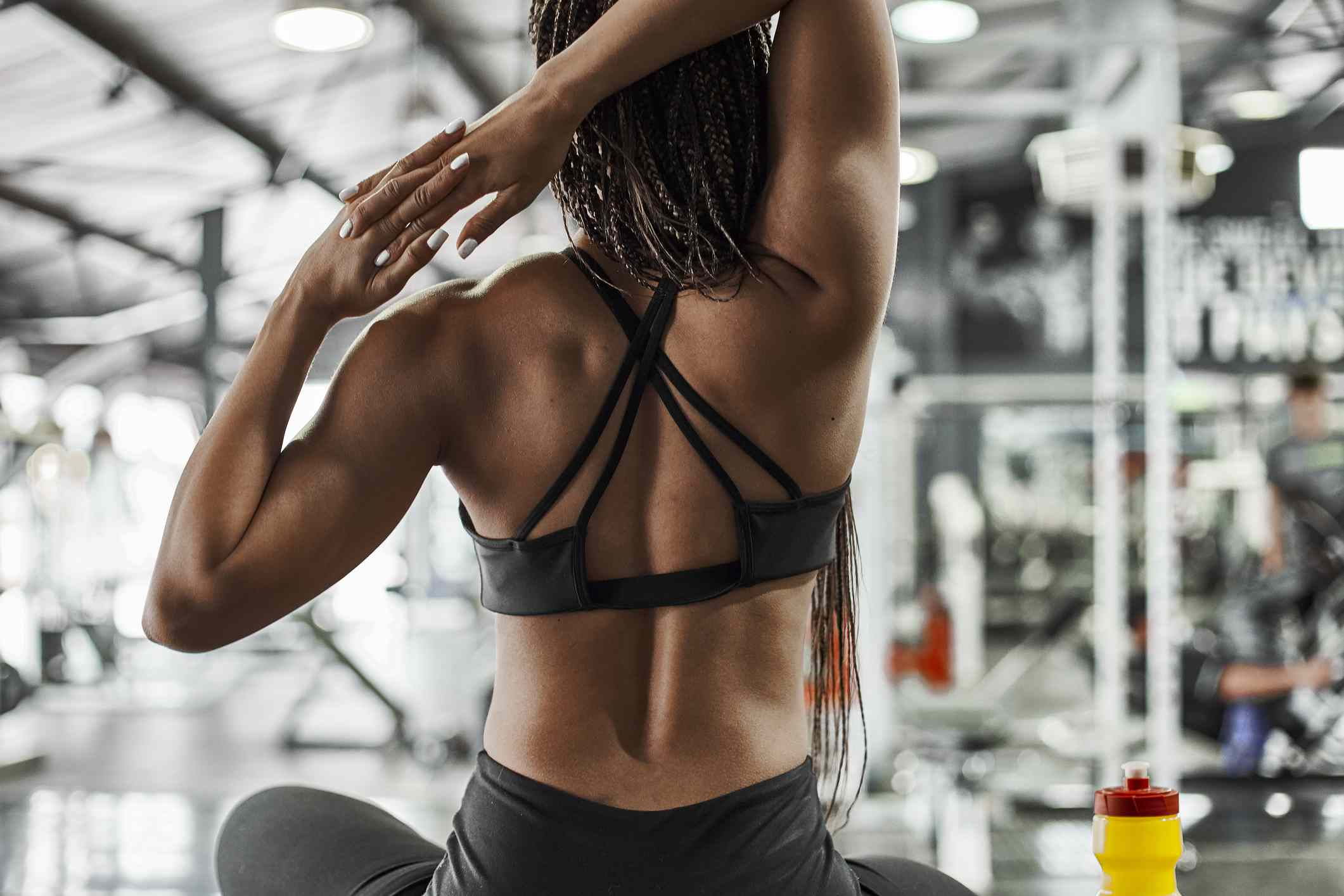 A woman stretching their muscles in the gym