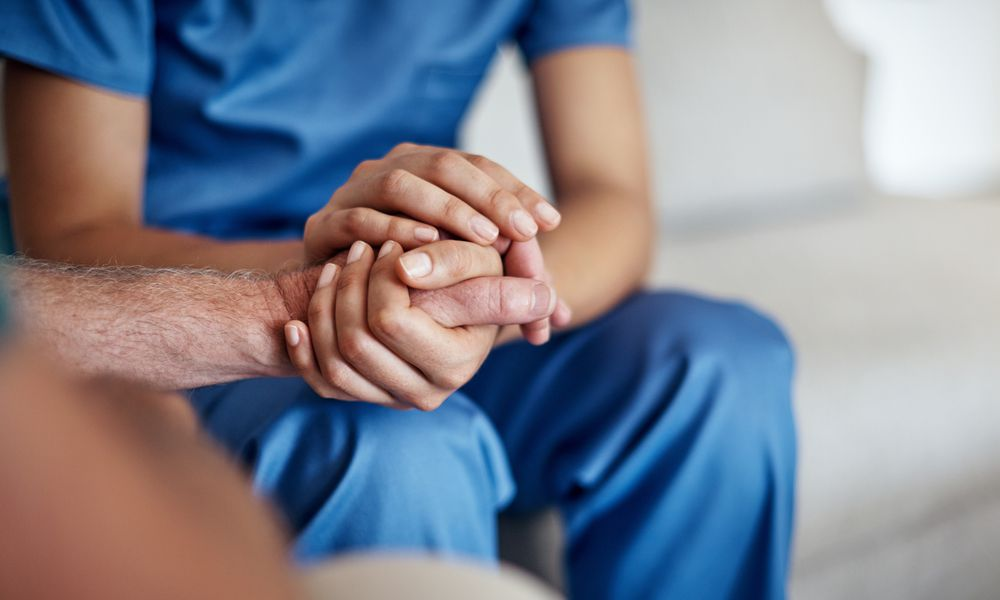 A person wearing scrubs holds the hand of another person.