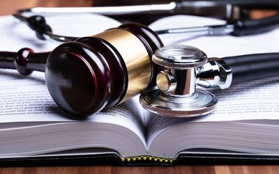 Stethoscope And Mallet Over Opened Law Book