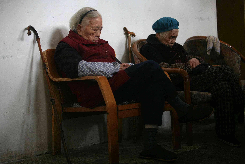 Two elderly women rest in their chairs