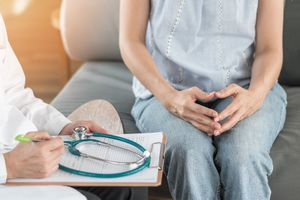 Anxious woman discussing late breast cancer recurrence with her doctor