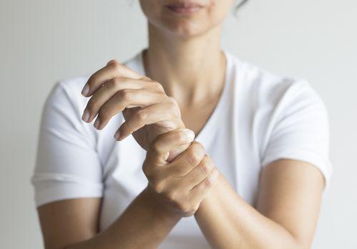 Wrist pain woman holding wrist