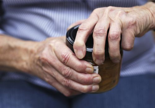 An older woman struggling to open a jar