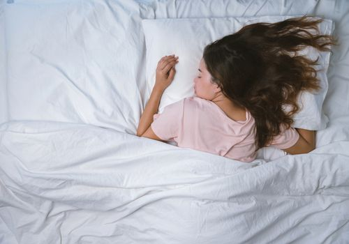 A woman with brown hair and light skin sleeping in bed