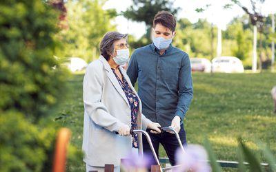Man helping older woman with walker wearing masks.