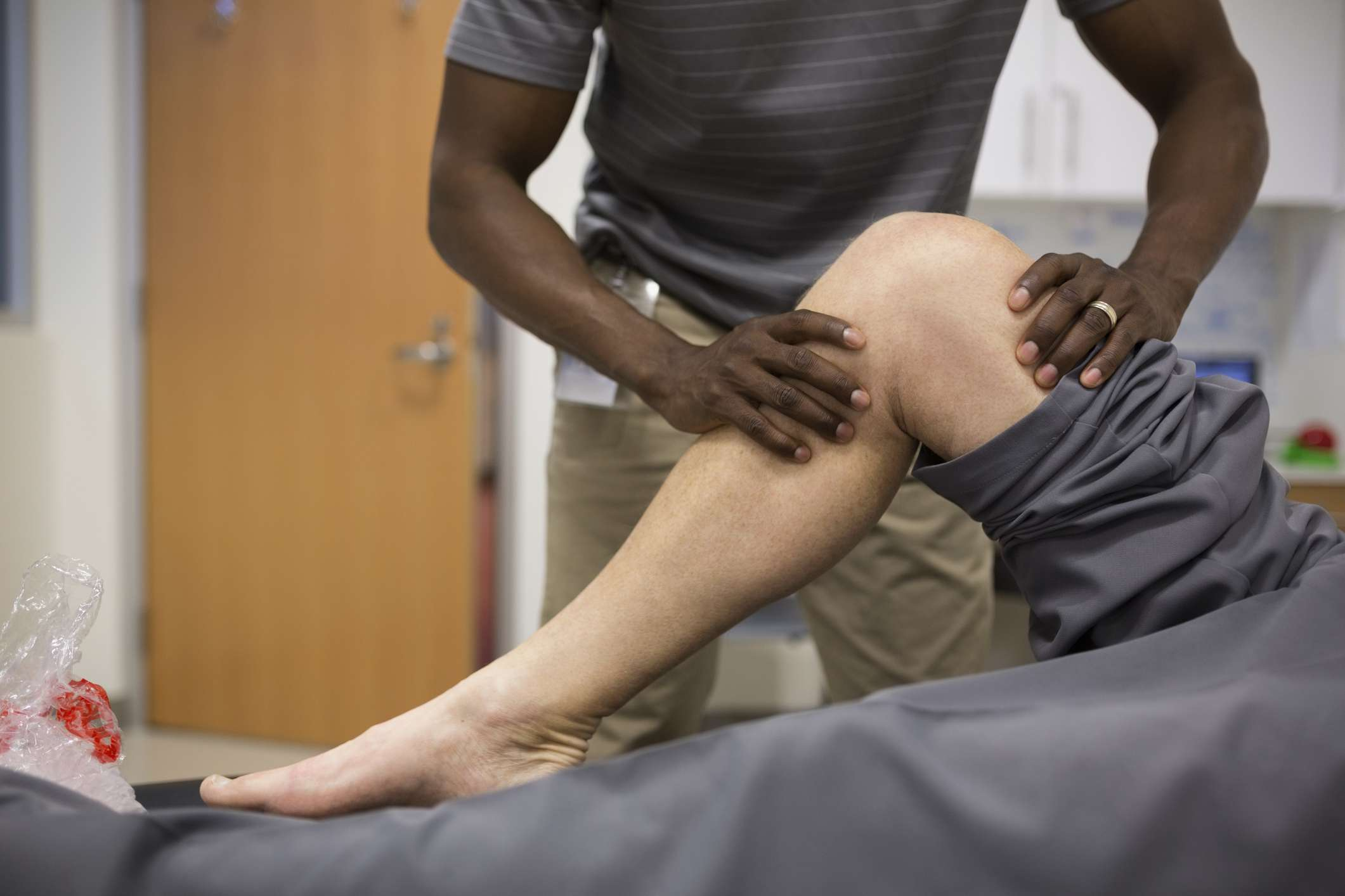 A physical therapist works on a patient's leg