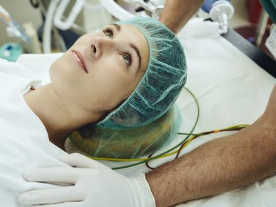 Operating nurse soothing patient on table in operating room