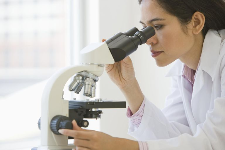 Female doctor using microscope