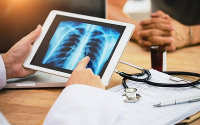 lung cancer concept. doctor explaining results of lung check up from x-ray scan chest on digital tablet screen to patient