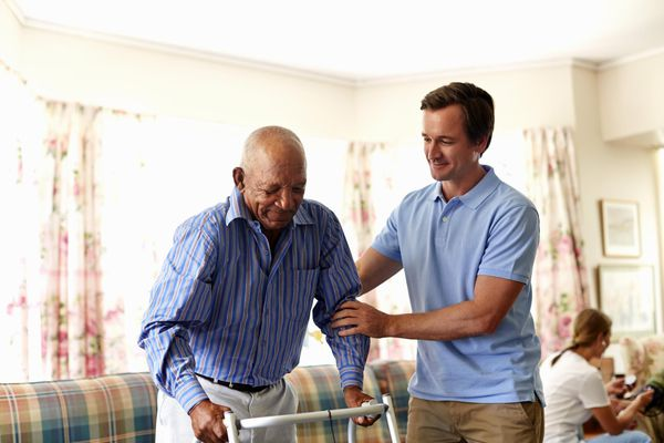 Man helping senior in assisted living home
