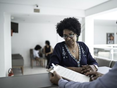Patient talking to the secretary at hospital reception