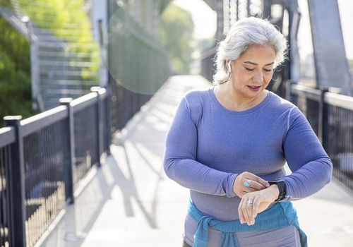 older woman tracking her exercise on smart watch