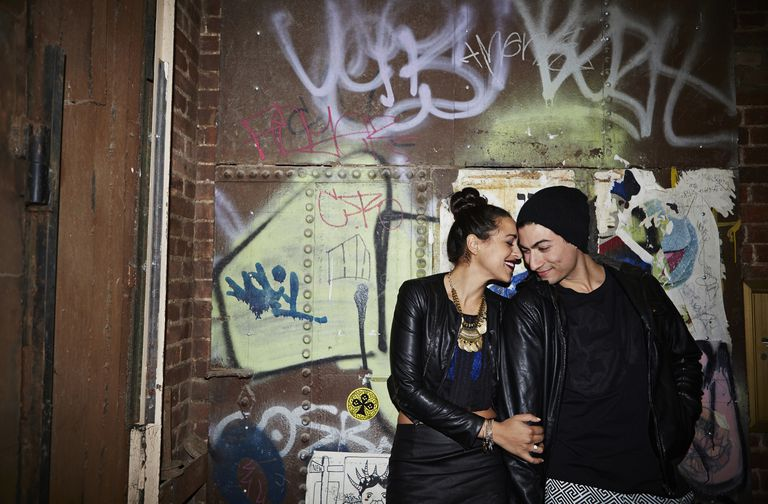 Couple in graffiti hallway standing close together